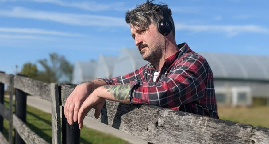 man by fence with headphones on