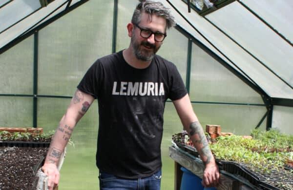 Kellen in front of plants in hoop house