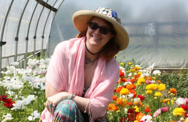 Tabitha in front of flowers in the hoop house