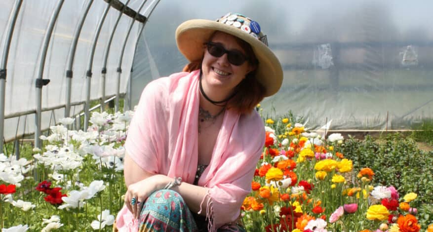 Tabitha Dial in front of flowers in the hoop house